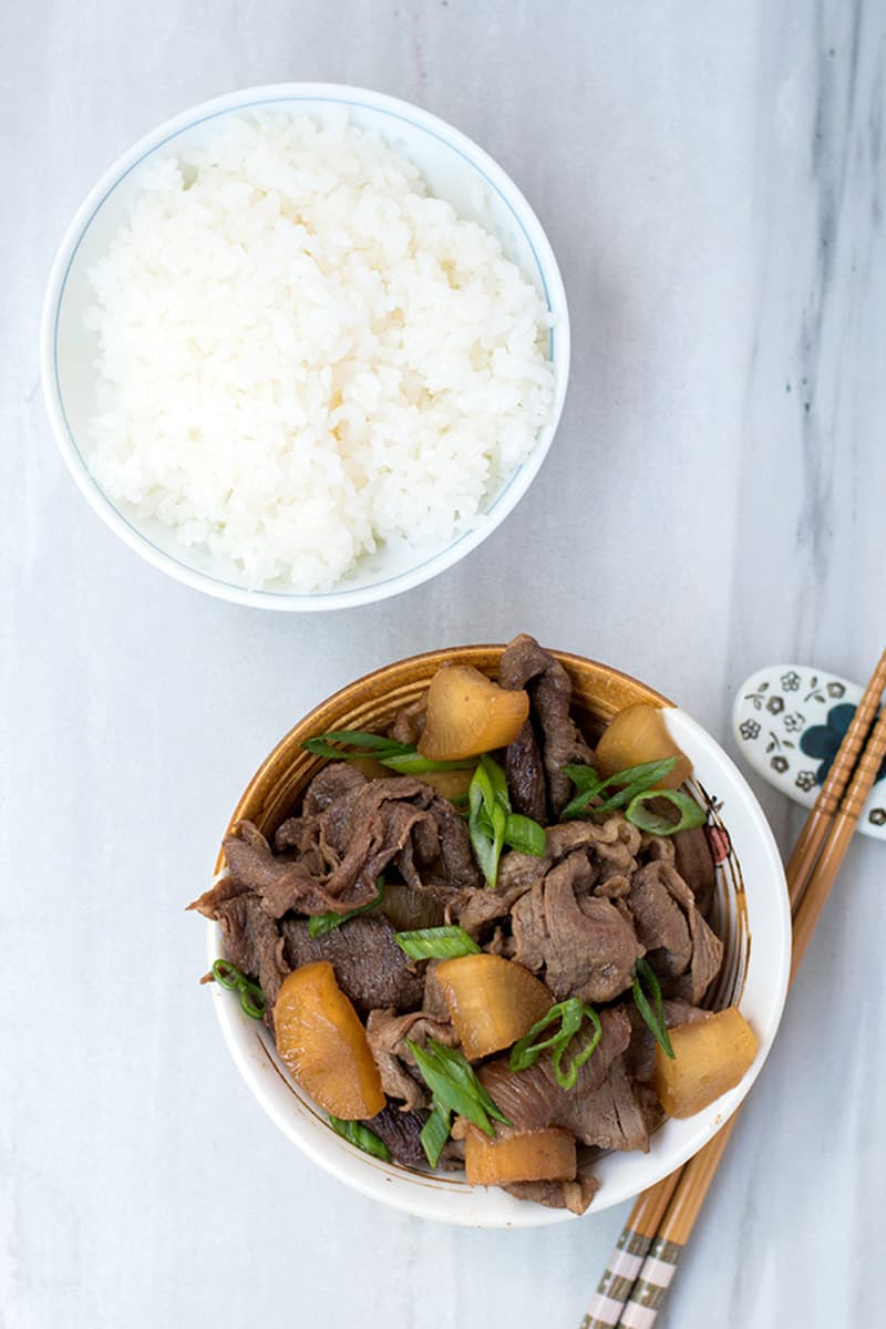 Top view of a bowl of beef with daikon stir fry with a bowl of rice and chopsticks next to it.