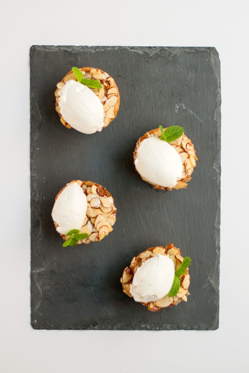 A cute almond tart made in a muffin tin. Tart crust, almond filling, and a glazed almond topping. Top with whipped cream for an elegant dessert.