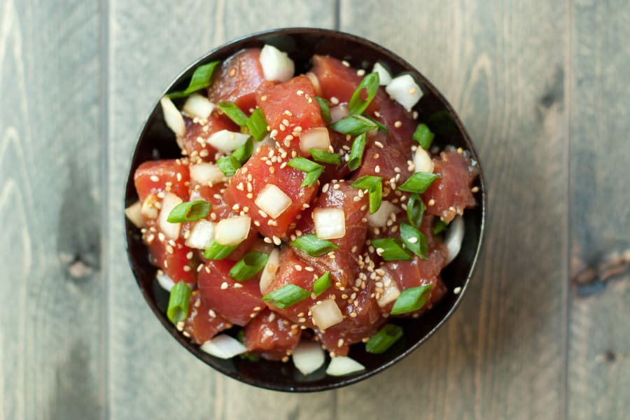 Top view of a bowl of ahi poke, garnished with sliced green onions and toasted sesame seeds.