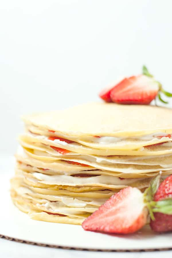 Finished product of strawberry crepe cake topped with a strawberry.