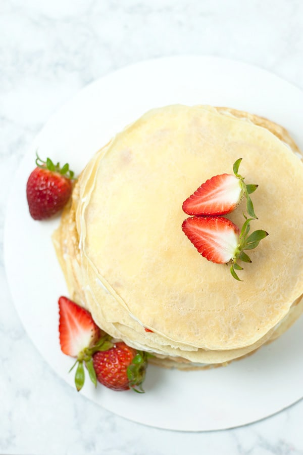 top view of whole strawberry crepe cake garnished with strawberry.