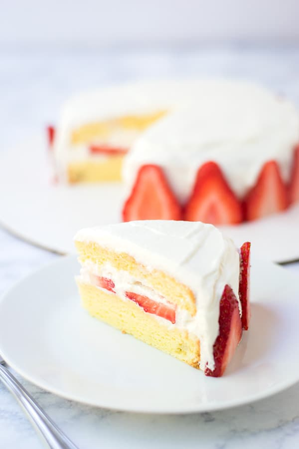 Slice of Japanese strawberry shortcake, with cake in the background.