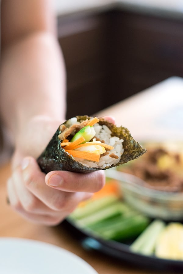Holding a canned tuna sushi hand roll with ingredients in background.