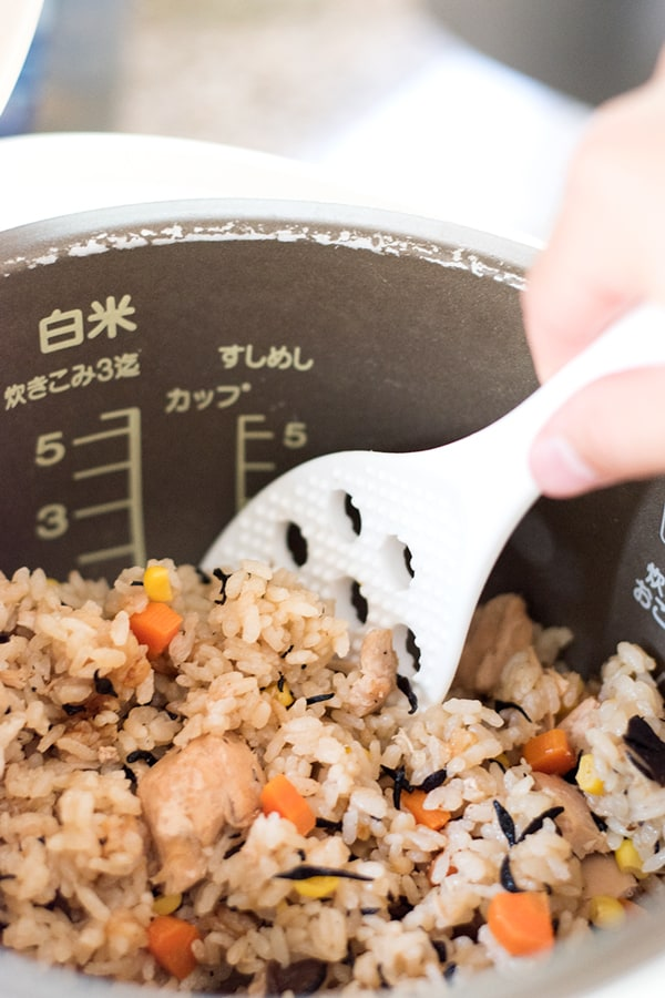 Tuna takikomi rice in rice cooker bowl, being scooped with rice paddle.