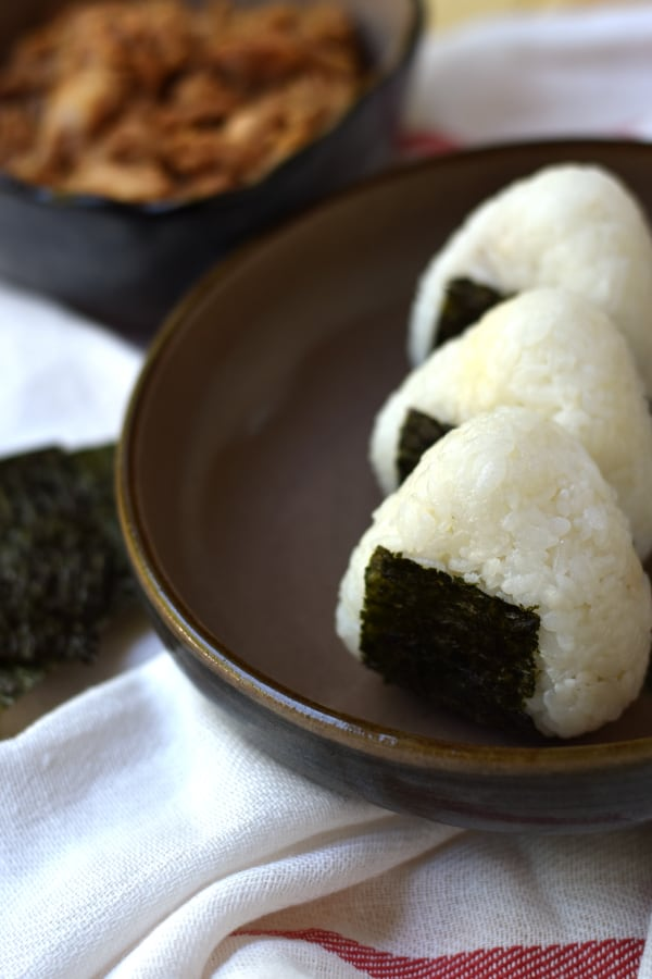 3 Tuna mayo onigiri lined up with a bowl of tuna in the background.