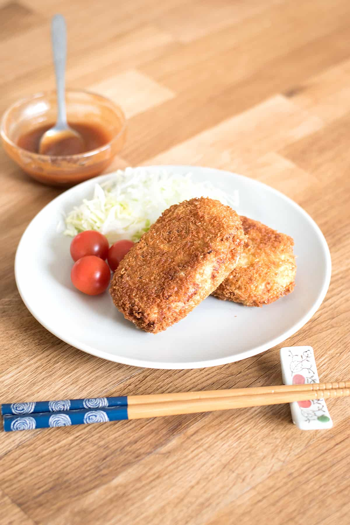 Finished picture of korokke dish (Japanese potato croquettes) with tonkatsu sauce in the background.