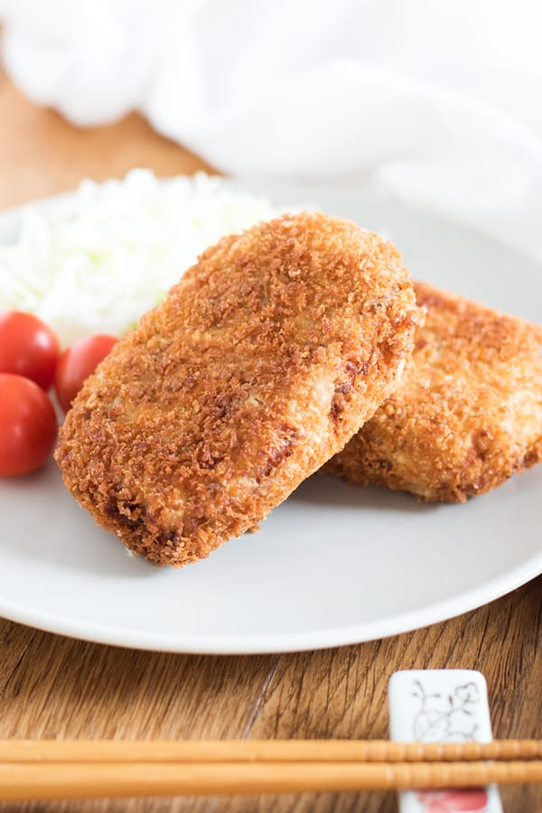 Korokke on a dish with cherry tomaties and shredded cabbage.