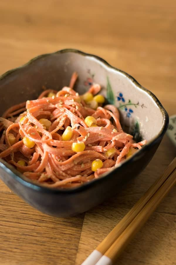 Japanese carrot salad in a bowl with chopsticks next to it.